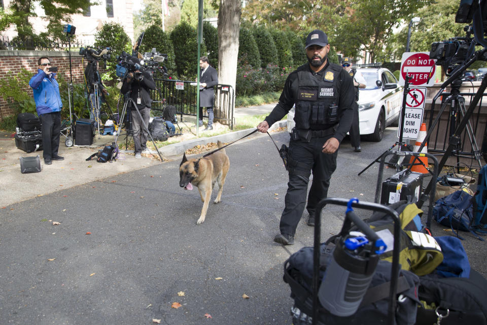 <em>An officer with the Uniform Division of the United States Secret Service uses his dog to search a checkpoint near the home of President Barack Obama (AP)</em>