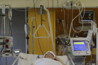 A COVID-19 patient lies on a bed in an intensive care unit (ICU) at Na Bulovce hospital in Prague, Czech Republic, Thursday, Oct. 1, 2020. A record surge of new coronavirus infections in the Czech Republic in September has been followed by a record surge of those hospitalized with COVID-19. The development has started to put the health system in the country under serious pressure for the first time since the pandemic hit Europe. (AP Photo/Petr David Josek)