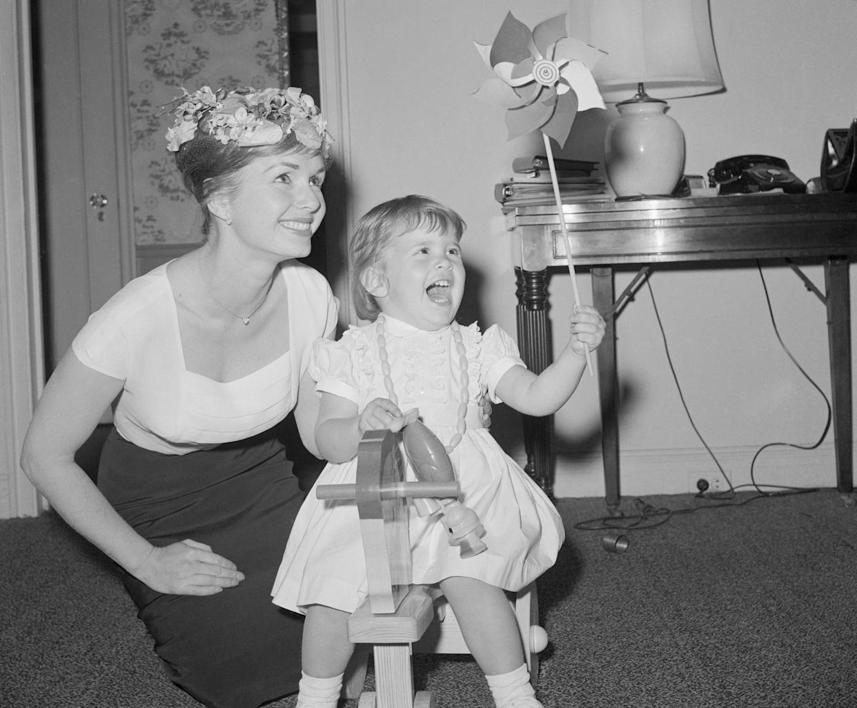 Debbie Reynolds is interviewed in her hotel room while 2-year-old Carrie squeals with delight and brandishes a pinwheel.