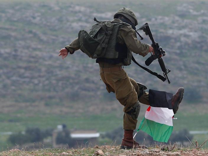 An Israeli soldier kicks a Palestinian flag in the Israeli-occupied West Bank on January 29.
