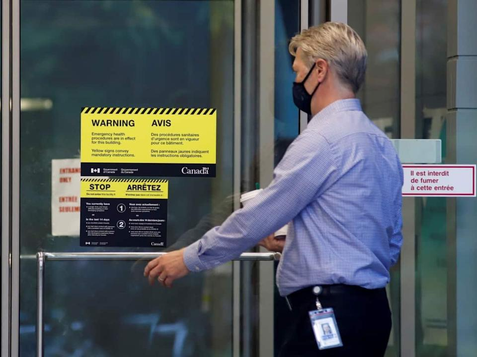 A worker enters a federal government building in Ottawa the same day Prime Minister Justin Trudeau announced all federal public servants will have to be fully vaccinated against COVID-19. (Patrick Doyle/Reuters - image credit)