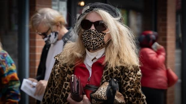 A person wears a leopard print coat, leopard print mask, hat and sunglasses in Ottawa's Centretown neighbourhood on May 11. (Brian Morris/CBC - image credit)