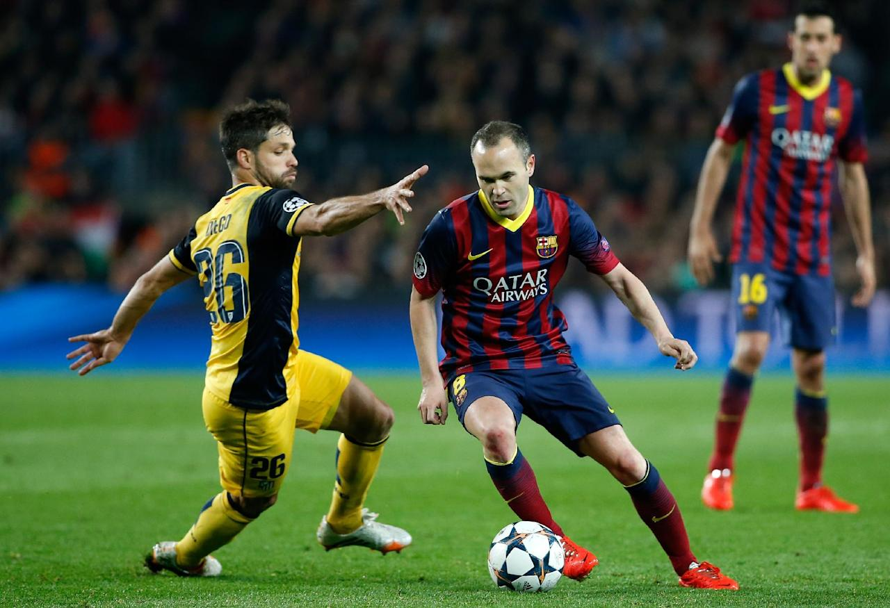 Barcelona's Andres Iniesta drives the ball past Atletico's Diego, left, during a first leg quarterfinal Champions League soccer match between Barcelona and Atletico Madrid at the Camp Nou stadium in Barcelona, Spain, Tuesday April 1, 2014. (AP Photo/Emilio Morenatti)