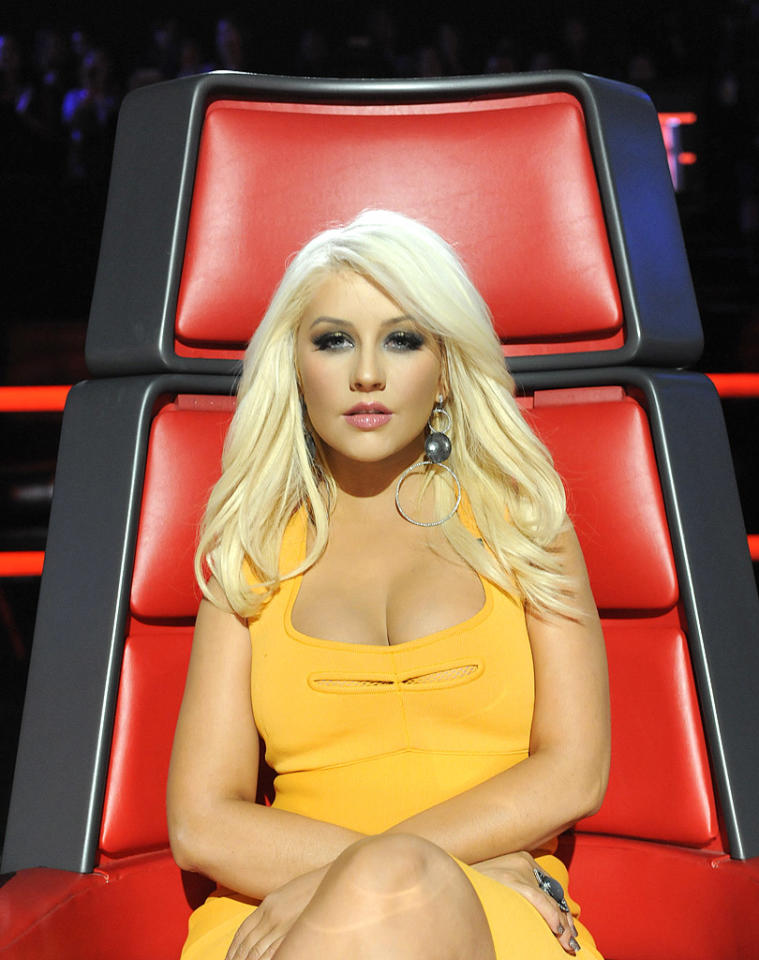 """Christina Aguilera looked sexier than ever on Tuesday night's episode of """"The Voice."""" The buxom coach -- who clearly hit the gym between the Battle Rounds and this week's live performances -- showed off her signature curves in a form-fitting, tangerine-hued frock. White-blond locks (which we happen to love), smokey eyes, statement earrings, and pouty pink lips completed the """"Beautiful"""" songstress' sultry ensemble. (4/3/2012) Follow 2 Hot 2 Handle creator, Matt Whitfield, on Twitter!"""