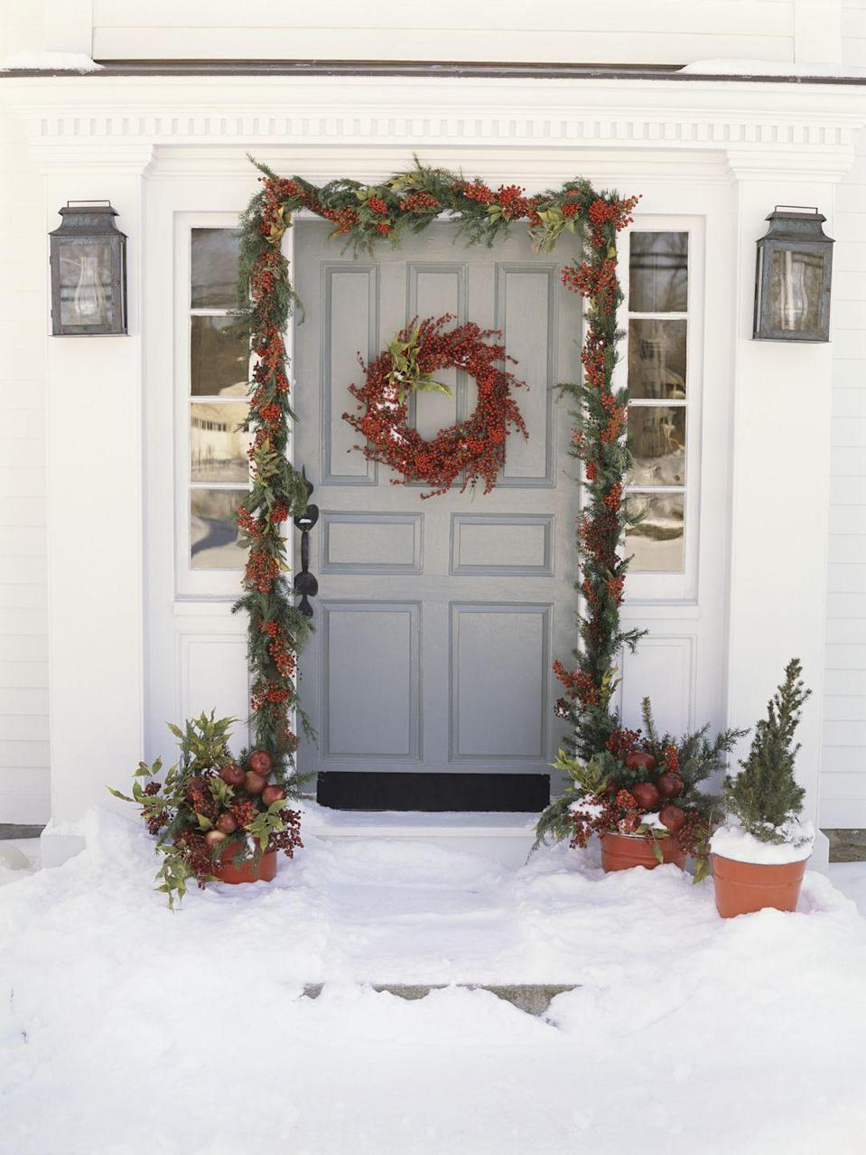 <p>The red accents of this berry-filled decor brings a natural pop of color to the festive front door.</p>
