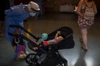 Spanish NGO Open Arms volunteer, Julia Martin, 38, plays with 4-month old Biel, as his father takes a COVID-19 PCR test, at Vilafranca del Penedes in the Barcelona province, Spain, Tuesday, Aug. 11, 2020. Spain is facing another surge in coronavirus infections not even two months after beating back the first wave. (AP Photo/Emilio Morenatti)