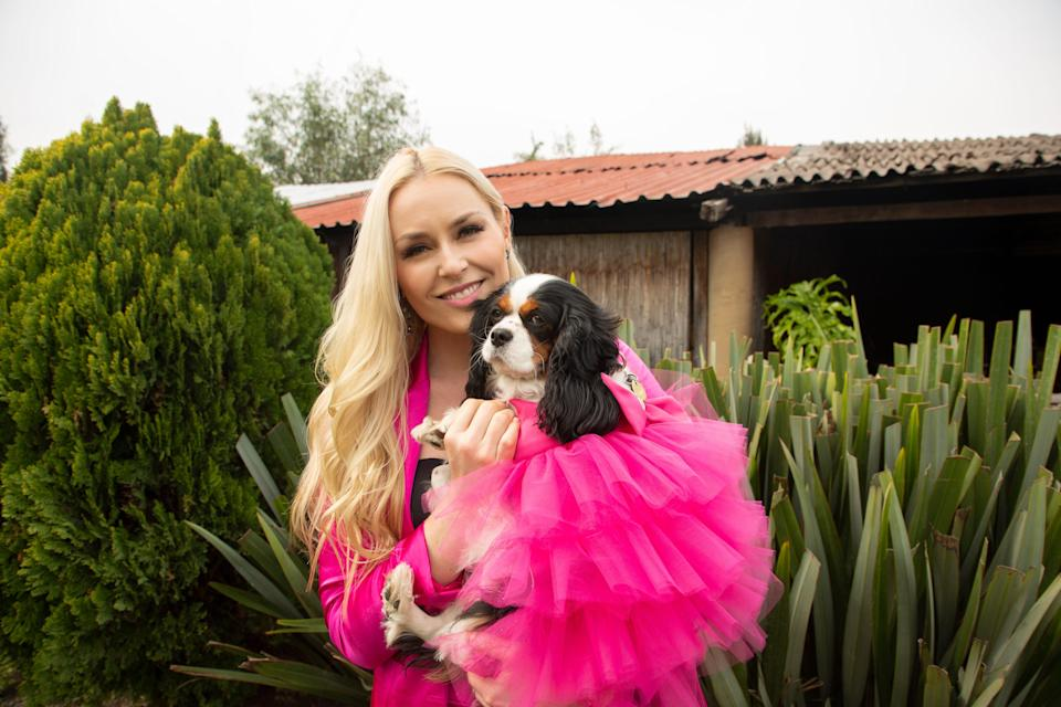 """""""The Pack"""" host Lindsey Vonn, with her co-host, her rescue dog Lucy oftentimes coordinate for the series. Lucy's fuchsia is one of Vonn's favorite costumes."""