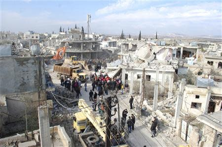 People gather around the wreckage of a car bomb in the village of Al-Kafat, in central Hama province January 9, 2014, in this handout photograph released by Syria's national news agency SANA. REUTERS/SANA/Handout via Reuters