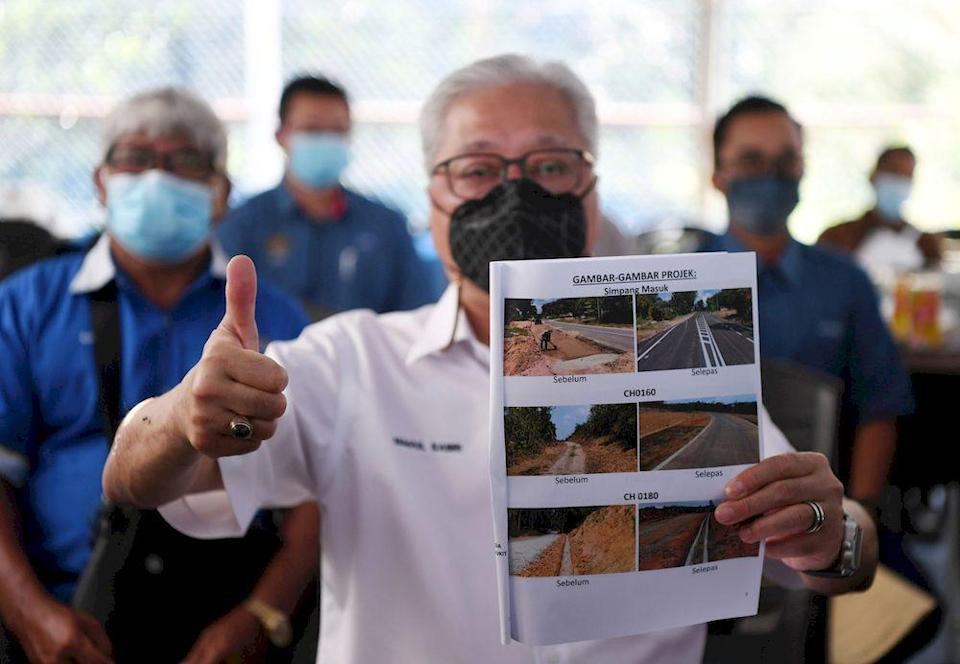 Senior Minister Datuk Seri Ismail Sabri Yaakob, who is also Bera Member of Parliament, showing before-and-after pictures of the road construction from Kampung Chuat to Kampung Bukit Imam Sulong, in Bera, April 11, 2021. — Bernama pic