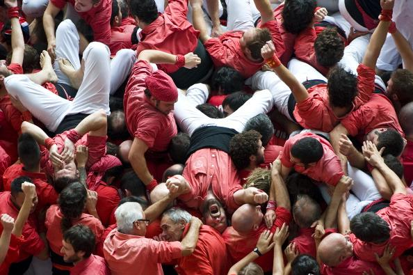 TARRAGONA, SPAIN - OCTOBER 07:  Members of the Colla 'Jove de Valls' celebrate after building a human tower during the 24th Tarragona Castells Comptetion on October 7, 2012 in Tarragona, Spain. The 'Castellers' who build the human towers with precise techniques compete in groups, known as 'colles', at local festivals with aim to build the highest and most complex human tower. The Catalan tradition is believed to have originated from human towers built at the end of the 18th century by dance groups and is part of the Catalan culture.  (Photo by David Ramos/Getty Images)
