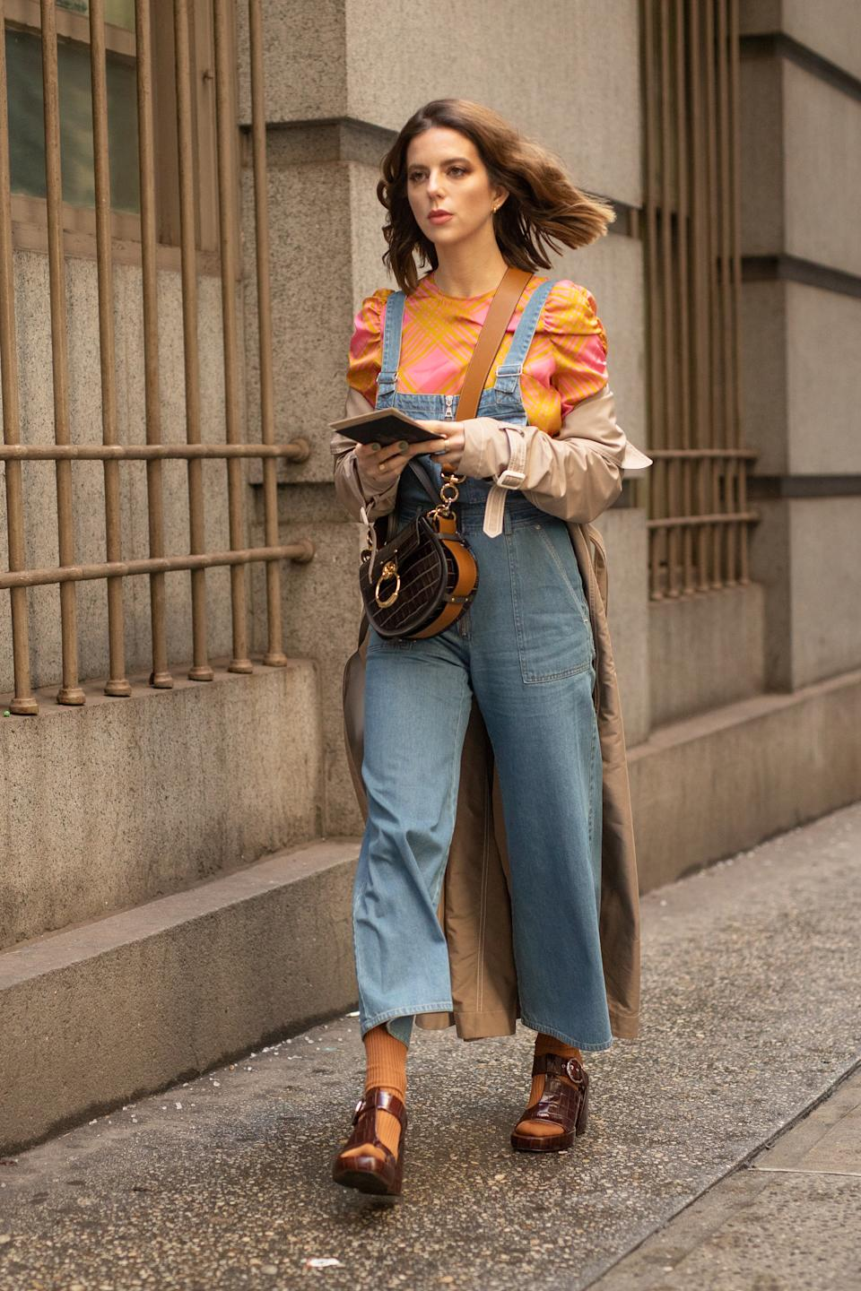 NEW YORK, NEW YORK - FEBRUARY 13: A guest is seen on the street during New York Fashion Week AW19 wearing denim overalls with orange ruffle shirt and brown heels on February 13, 2019 in New York City. (Photo by Matthew Sperzel/Getty Images)