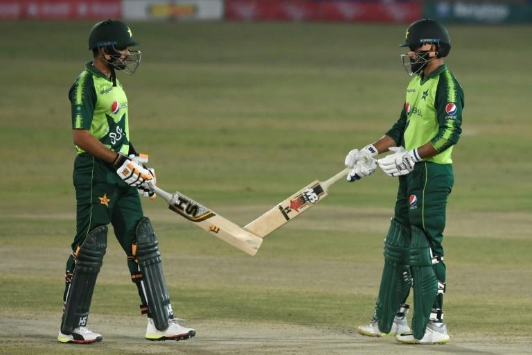 Pakistan's Mohammad Hafeez (right) celebrates with captain Babar Azam after hitting a six during his 36 against Zimbabwe