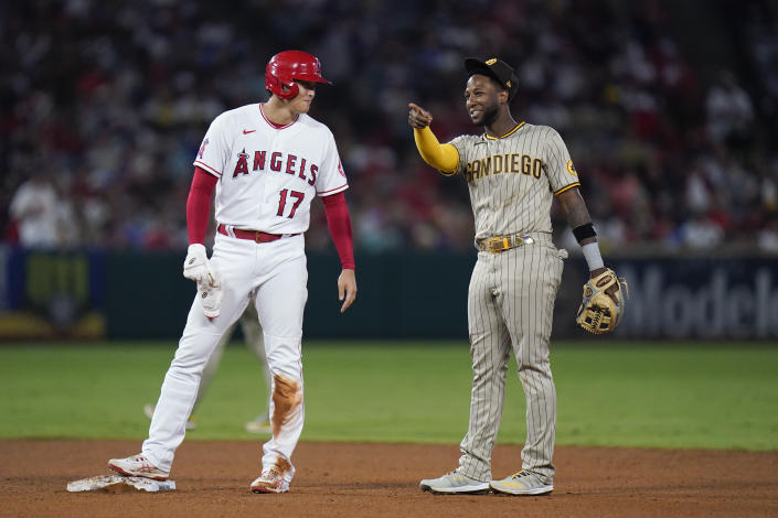 Los Angeles Angels' Shohei Ohtani, left, of Japan, shares a light moment with San Diego Padres' Jurickson Profar after stealing second base during the fifth inning of a baseball game in Anaheim, Calif., Saturday, Aug. 28, 2021. (AP Photo/Jae C. Hong)