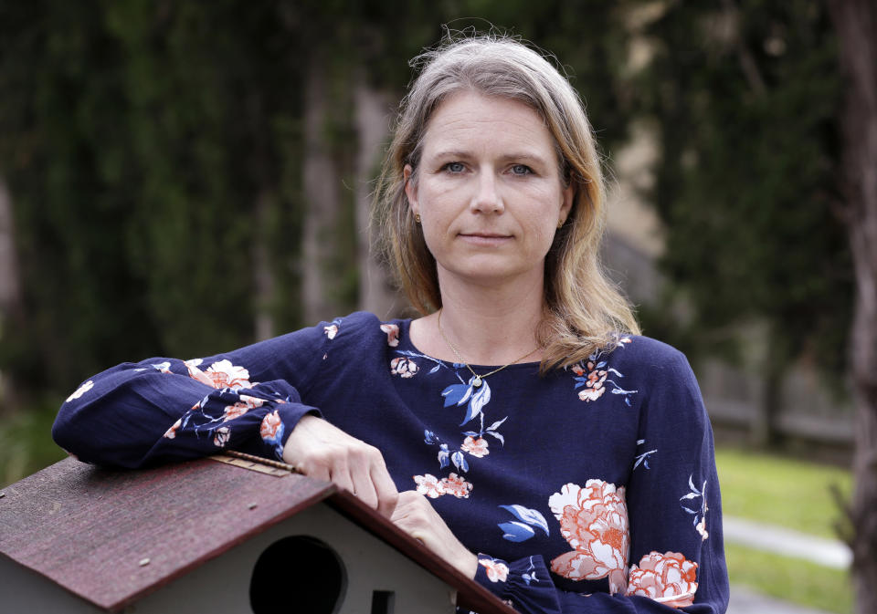 Astrid Magenau poses for a photo at her home in Sydney on Oct. 19, 2020. Magenau wasn't able to keep a promise to hold her father's hand at his deathbed in Germany because of Australia's extraordinary pandemic restrictions that make her feel like a prisoner in her adopted country. (AP Photo/Rick Rycroft)