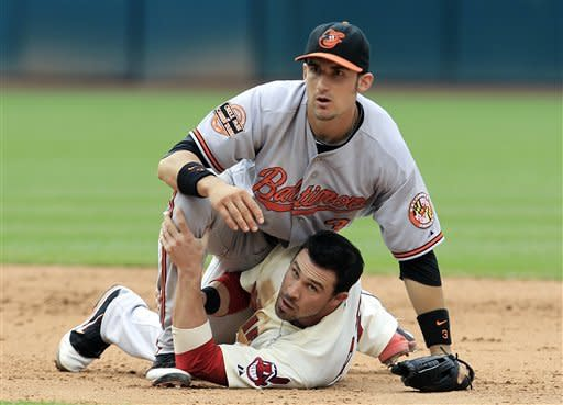 Baltimore Orioles' Ryan Flaherty, top, and Cleveland Indians' Jason Kipnis look toward first base in the sixth inning in a baseball game, Sunday, July 22, 2012, in Cleveland. Kipnis was out at second base on a fielder's choice. Jose Lopez was safe at first base. (AP Photo/Tony Dejak)