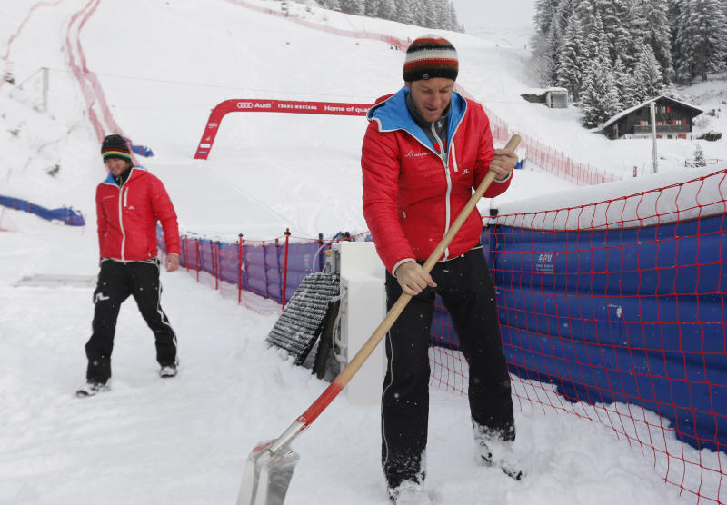 Men at work as fresh snow in conjunction with the too soft base in the lower section of the course forced the jury to cancel a training for the women's alpine skiing World Cup downhill race in Crans-Montana, Switzerland, Friday, Feb. 28, 2014. (AP Photo/Marco Trovati)