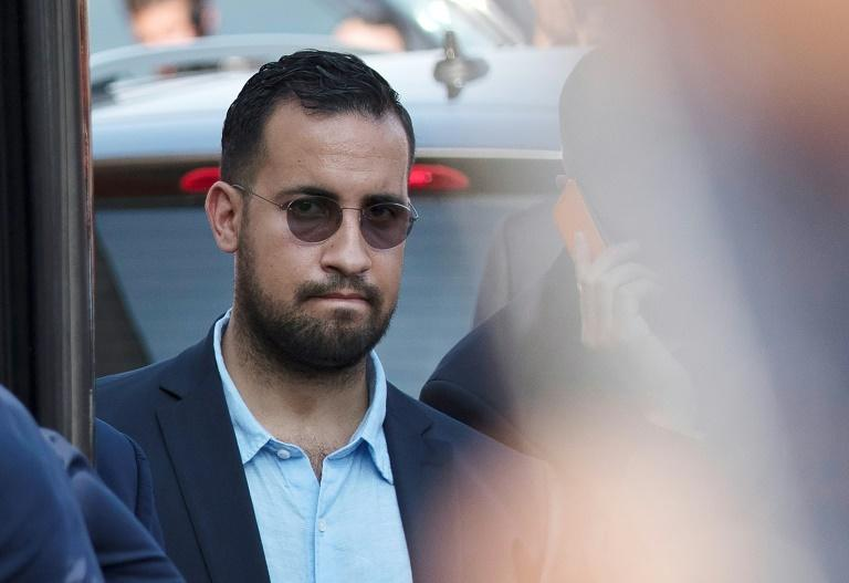 (FILES) In this file photo taken on July 16, 2018 Elysee senior security officer Alexandre Benalla stands next to a bus and the plane transporting the France's national football team at the Roissy-Charles de Gaulle airport on the outskirts of Paris, after French players won the Russia 2018 World Cup final football match. Alexandre Benalla has refused to appear before the Senate commission before the end of the judicial investigation, his lawyer said on September 11, 2018