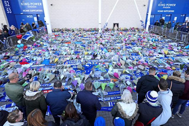 <p>Supporters pay tribute at Leicester City following a helicopter used by club owner Vichai Srivaddhanaprabha, crashing into flames in a car park near the stadium shortly after 8.30pm on Saturday evening. Aaron Chown/PA Wire </p>