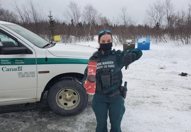 Park Warden Janelle MacLeod poses for a photo holding garbage she found on the side of the road in Terra Nova National Park.