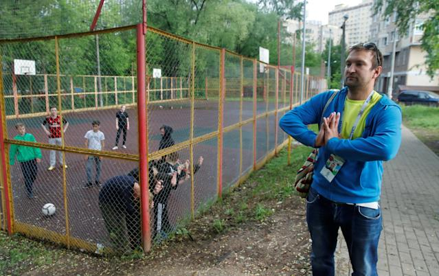 Soccer fan Pavel Cherkas, who was blacklisted by Russian authorities for bad behaviour at a stadium, stands near a football ground while wearing his 2018 World Cup fan ID, which was granted to Cherkas and later revoked, during an interview outside Moscow, Russia May 20, 2018. Picture taken May 20, 2018. REUTERS/Maxim Shemetov