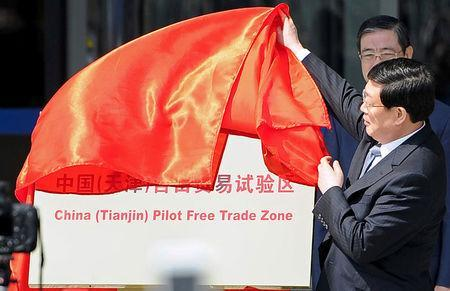 """FILE PHOTO: Tianjin municipal Mayor Huang Xingguo removes the veil covering a sign reading """"China (Tianjin) Pilot Free Trade Zone"""", at an unveiling ceremony in Tianjin municipality, April 21, 2015. REUTERS/Stringer/File Photo"""