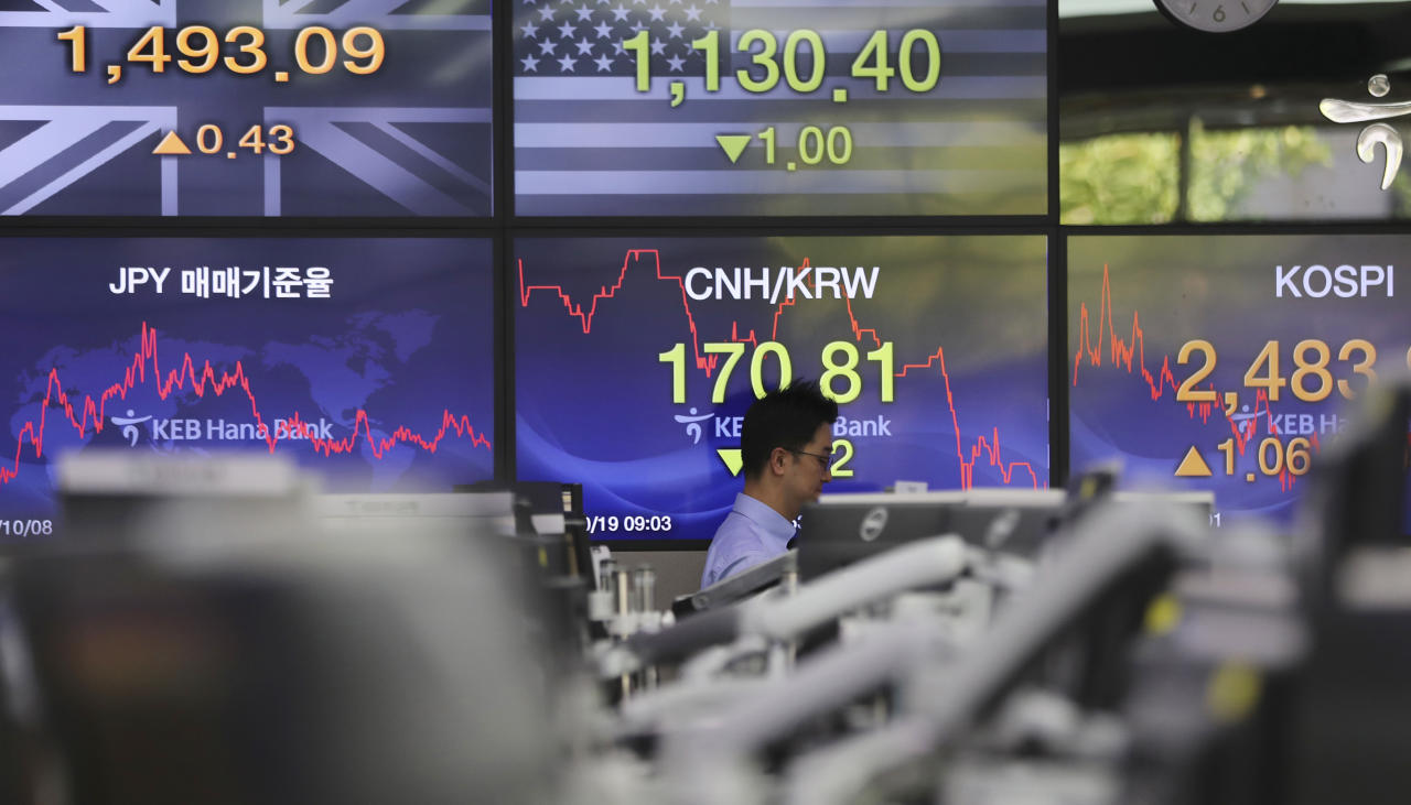 A currency trader walks by the screens showing the Korea Composite Stock Price Index (KOSPI), right, and the foreign exchange rates at the foreign exchange dealing room in Seoul, South Korea, Thursday, Oct. 19, 2017. Asian markets were mixed on Thursday after Wall Street closed at record highs. Data showed that China's quarterly growth slowed slightly but was in line with expectations. (AP Photo/Lee Jin-man)
