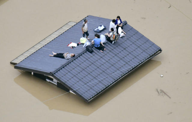 <p>People waif to be rescued on the top of a house almost submerged in floodwaters caused by heavy rains in Kurashiki, Okayama prefecture, southwestern Japan, Saturday, July 7, 2018. (Photo: Shingo Nishizume/Kyodo News via AP) </p>