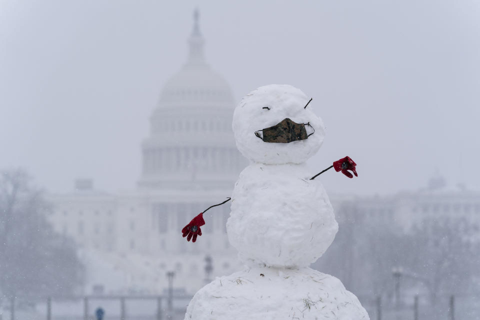 A snowman on the National Mall wears a face mask as snow falls in front of the U.S. Capitol, Sunday, Jan. 31, 2021, in Washington. (AP Photo/Alex Brandon)