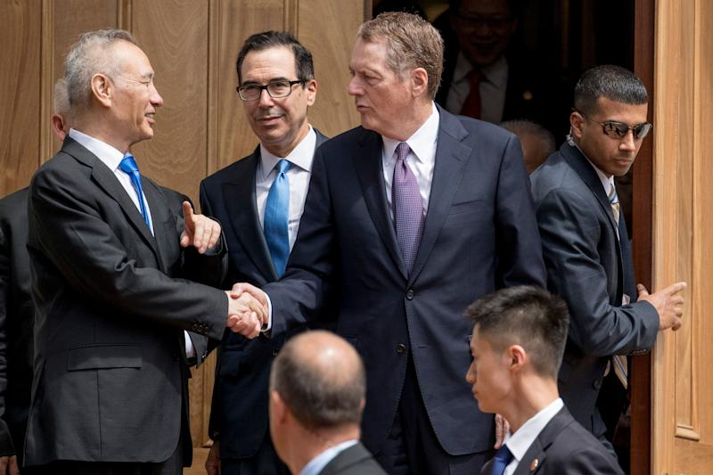 Treasury Secretary Steve Mnuchin, center, and United States Trade Representative Robert Lighthizer, third from left, and Chinese Vice Premier Liu He, left, speak together as Liu He departs the Office of the United States Trade Representative in Washington, Friday, May 10, 2019. (AP Photo/Andrew Harnik)