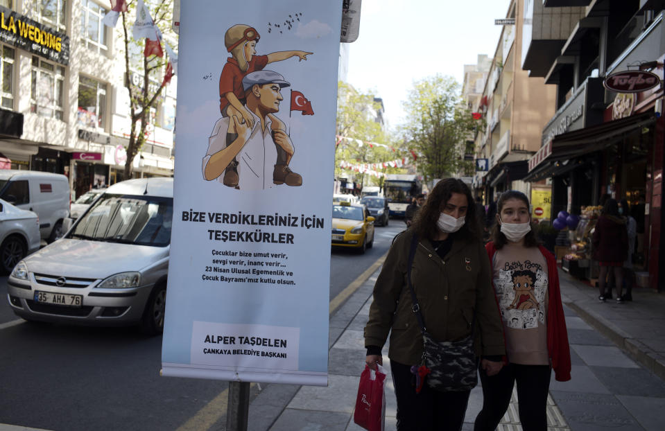 People wearing masks to help protect against the spread of coronavirus, walk along a busy street before a nationwide lockdown, in Ankara, Turkey, Thursday, April 22, 2021. Turkey has announced that it is extending an upcoming weekend lockdown to include a public holiday on Friday, as it grapples with soaring infections. The country has been posting record-high levels of infections and deaths since it eased COVID-19 restrictions in early March. The poster is depicting Turkey's founder Kemal Ataturk holding a child.(AP Photo/Burhan Ozbilici)