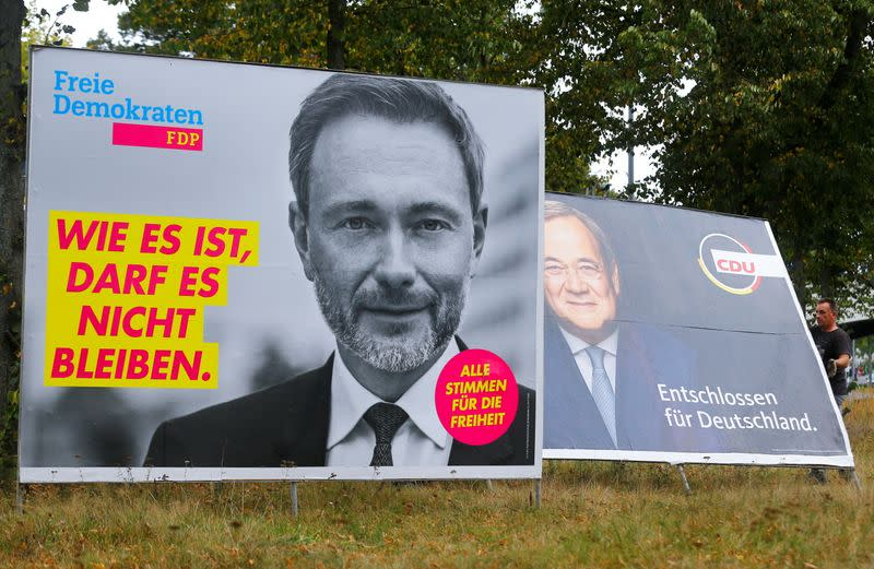 FILE PHOTO: Workers remove election campaign posters showing Free Democratic Party (FDP) leader Christian Lindner (L) and Armin Laschet, chancellor candidate for Germany's Christian Democratic Union (R), the day after the general election, in Cologne, Germ
