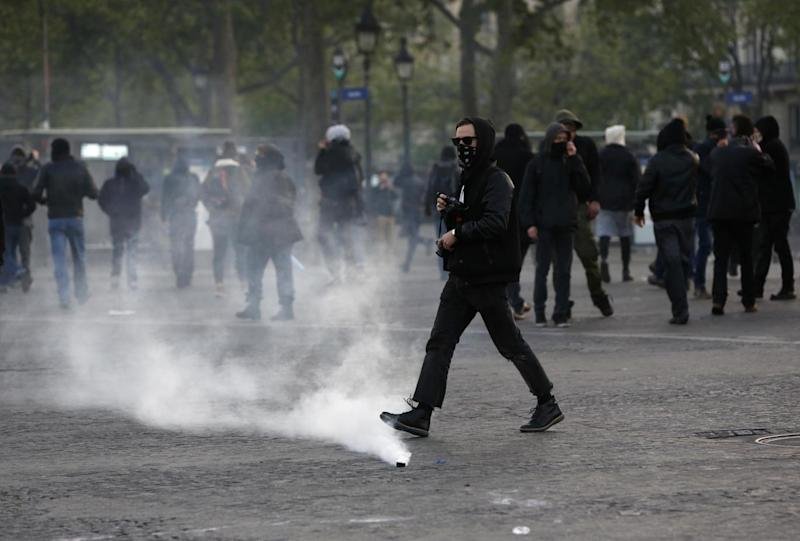 Trouble: Youths walk near tear gas grenades as they scuffle with riot police officers during a protest against Ms Le Pen in Paris (AP)