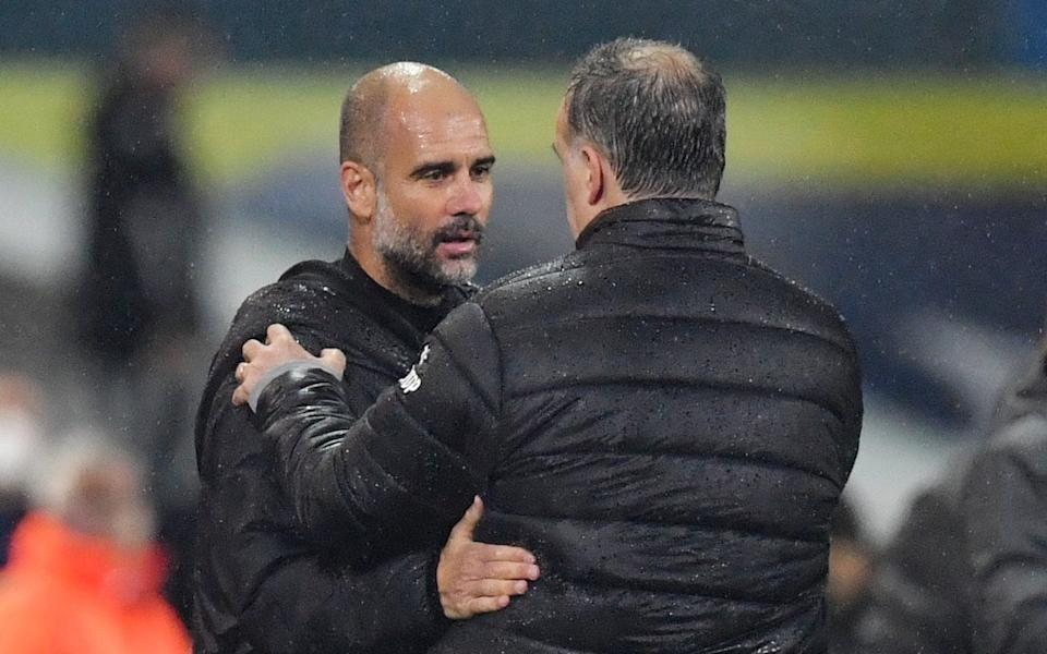 The two managers embrace at full-time having watched their sides play out an entertaining 90 minutes - REUTERS