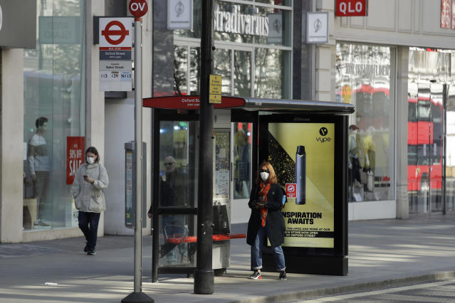 A masked woman waits at a bus stop on a deserted Oxford Street in London. (AP)