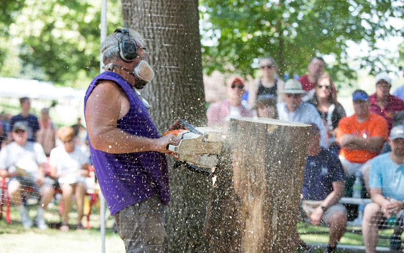 Gary Keenan uses a chainsaw to carve a Moai (think Easter Island) out of wood. Gary and his team do chainsaw carving presentations each day of the fair and then auction off their creations on the last day. | Jason Bergman