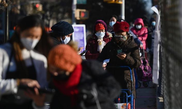 People stand in line at a food distribution event ahead of the Thanksgiving holiday on Friday in Brooklyn, New York.