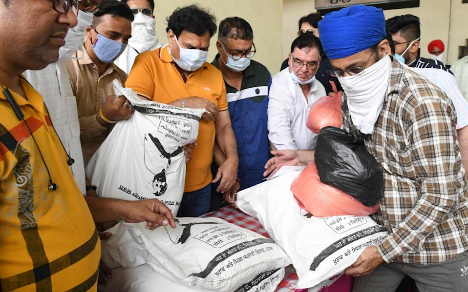 Officials distribute food items and money to relatives of Covid-19 patients in Amritsar, India on June 13 2021 - Narinder Nanu/AFP