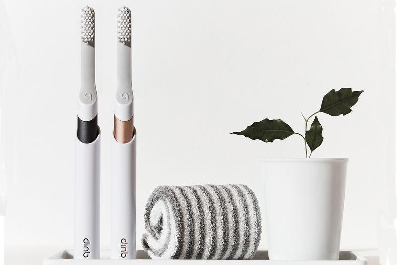 Two Quip toothbrushes, a towel, and a plant