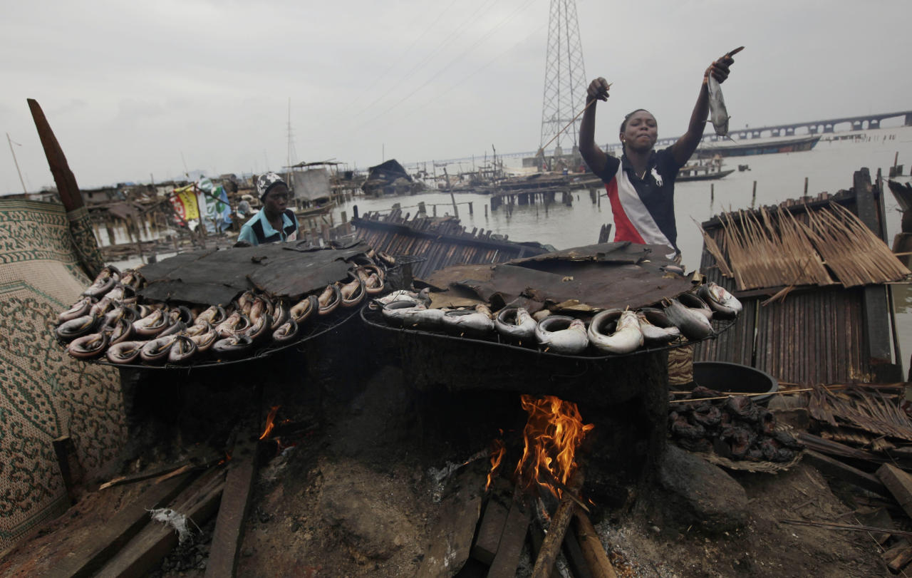 In this photo taken Thursday, July 26, 2012, a woman gestures as she smokes fish at her demolished stilts house at Makoko in Lagos, Nigeria. The teeming, floating Makoko slum rises out of the murky lagoon water that separates mainland Nigeria from the island that gave birth to its largest city, a permanent haze of smoke rising from its homes built on timber stilts. A government-led eviction last week that saw men in speedboats destroy homes with machetes there left about 3,000 people homeless and raised new fears among activists that authorities may try to wipe it out the area entirely. (AP Photo/Sunday Alamba)