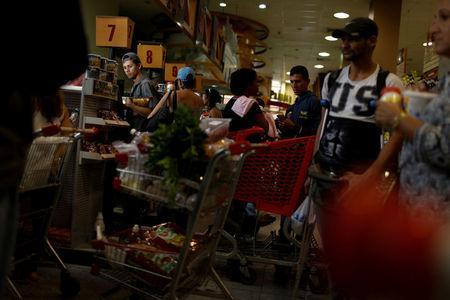 A man waits in line to pay for food at the cashier of a supermarket in Caracas, Venezuela March 10, 2017. REUTERS/Carlos Garcia Rawlins