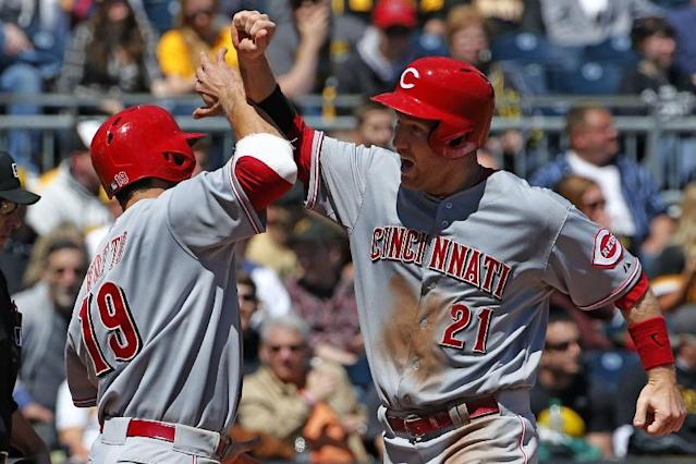 Cincinnati Reds' Todd Frazier (21) celebrates with Joey Votto (19) after they scored on a double by Reds' Ryan Ludwick off Pittsburgh Pirates starting pitcher Brandon Cumpton during the sixth inning of a baseball game in Pittsburgh Thursday, April 24, 2014. (AP Photo/Gene J. Puskar)