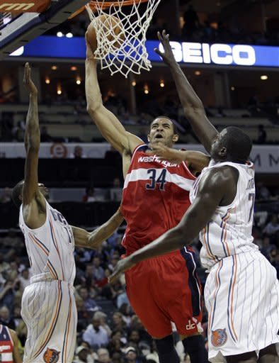 Washington Wizards' JaVale McGee, center, shoots over Charlotte Bobcats' DeSagana Diop, right, and Tyrus Thomas, left, during the second half of the Wizards' 102-99 win in an NBA basketball game in Charlotte, N.C., Saturday, Jan. 28, 2012. (AP Photo/Chuck Burton)