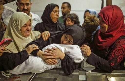 The body of a Palestinian baby who died of tear gas inhalation during protests, according to Gaza's health ministry, is held by her mother at a Gaza City morgue on May 15, 2018
