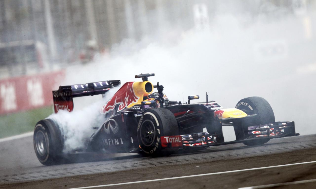 Red Bull Formula One driver Sebastian Vettel of Germany does a burnout to celebrate winning the Indian F1 Grand Prix at the Buddh International Circuit in Greater Noida, on the outskirts of New Delhi, October 27, 2013. Vettel became Formula One's youngest four-times world champion on Sunday after winning the Indian Grand Prix for Red Bull. REUTERS/Anindito Mukherjee (INDIA - Tags: SPORT MOTORSPORT F1 TPX IMAGES OF THE DAY)