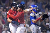 Boston Red Sox's Alex Verdugo, center, is congratulated by Hunter Renfroe, left, after his two-run home run in the eighth inning of a baseball game against the Toronto Blue Jays at Fenway Park, Monday, July 26, 2021, in Boston. Blue Jays catcher Reese McGuire, right, looks on. (AP Photo/Charles Krupa)