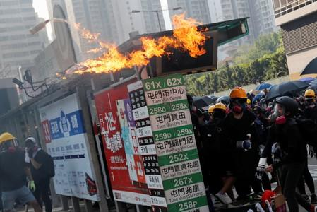 An anti-government protester throws a molotov cocktail during a demonstration on China's National Day, in Wong Tai Sin, Hong Kong