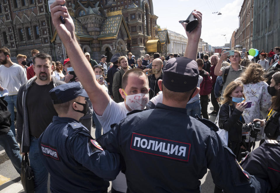 Police block protesters during a rally supporting Khabarovsk region's governor Sergei Furgal in St.Petersburg, Russia, Saturday, Aug. 1, 2020. Thousands of demonstrators rallied Saturday in the Russian Far East city of Khabarovsk to protest the arrest of the regional governor, continuing a three-week wave of opposition that has challenged the Kremlin. (AP Photo/Dmitri Lovetsky)