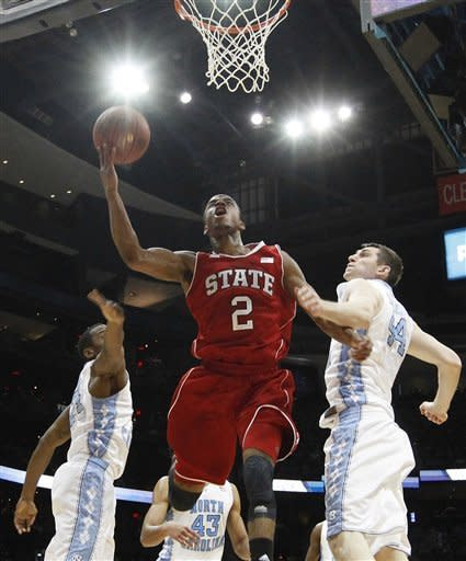 North Carolina guard Justin Watts, left, and forward Tyler Zeller (44) defend as North Carolina State guard Lorenzo Brown (2) heads to the hoop during the first half of an NCAA college basketball game in the semifinals of the Atlantic Coast Conference tournament, Saturday, March 10, 2012, in Atlanta. (AP Photo/John Bazemore)