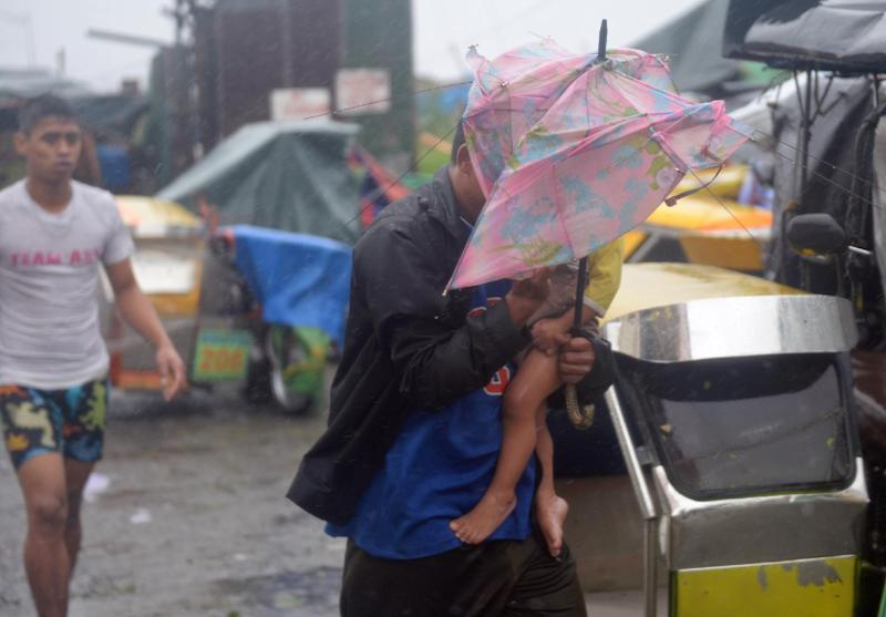 Residents brave strong winds and rain as they evacuate from homes in a slum area as Typhoon Rammasun barrels across Manila on July 16, 2014 (AFP Photo/Ted Aljibe)