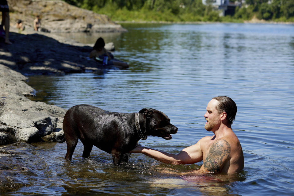 Justin Swanner and his dog Havoc swim in the Clackamas River to escape from the heat during a record setting heat wave in Oregon City, Ore., Sunday, June 27, 2021. Yesterday set a record high for the day with more records expected today. (AP Photo/Craig Mitchelldyer)